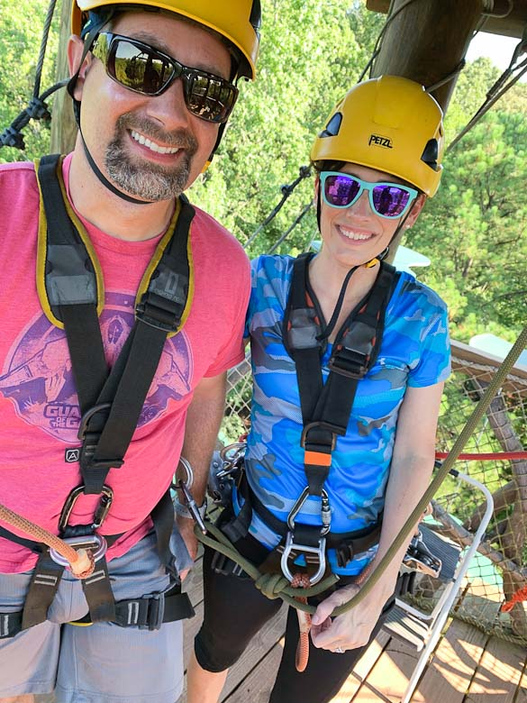 Two people with helments on ready for zipline adventure