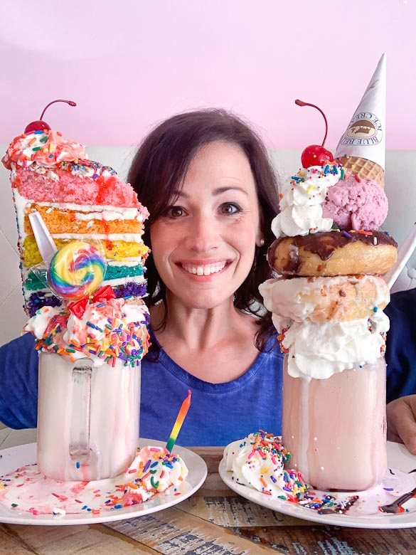 Lady with two colossal milkshakes, one with birthday cake on top and the other with donuts