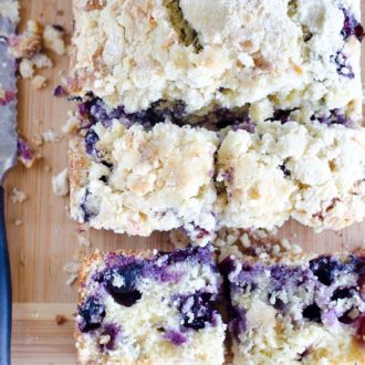 Slices of blueberry muffin bread on cutting board with knife.