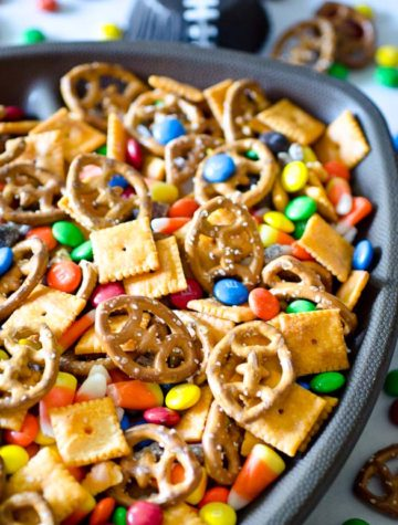 Snack mix with football shaped pretzels in a football shaped bowl.
