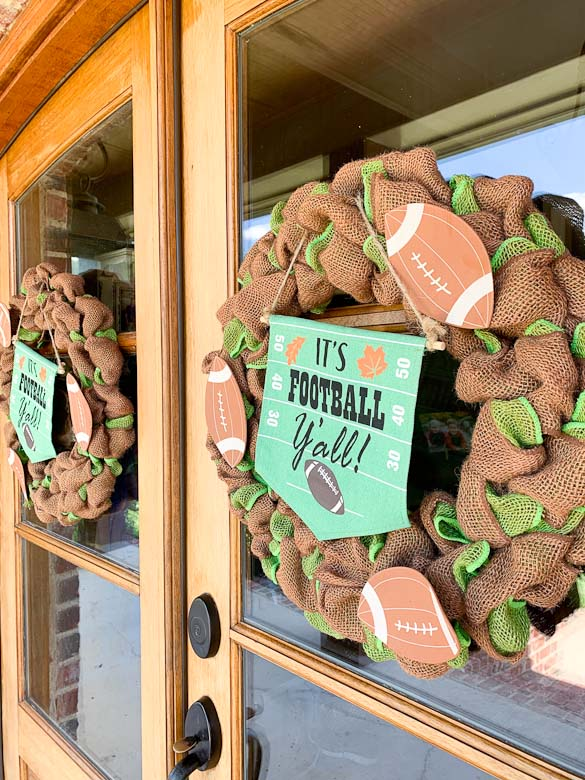 Two football burlap wreaths hanging on double front doors