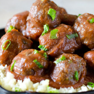 Sweet and sour meatballs stacked in a skillet with cauliflower rice
