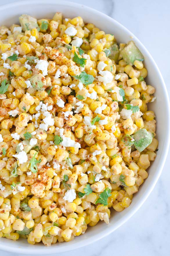 bowl of corn salad with mexican spices, avocado and cheese
