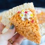 holding rice krispies treats shaped as pumpkin pie slice