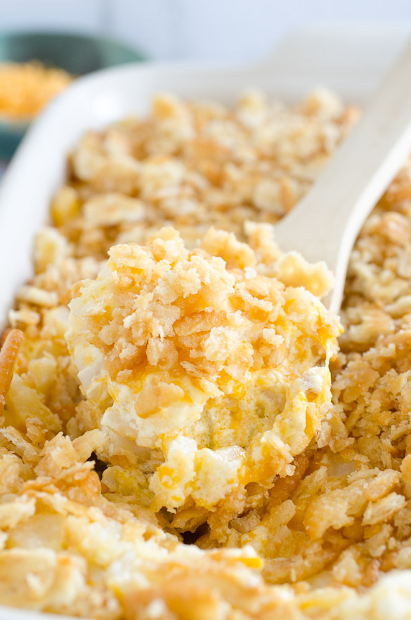 wooden spoon full of cheesy potatoes with ritz cracker topping