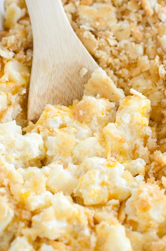 wooden spoon in cheesy potato dish