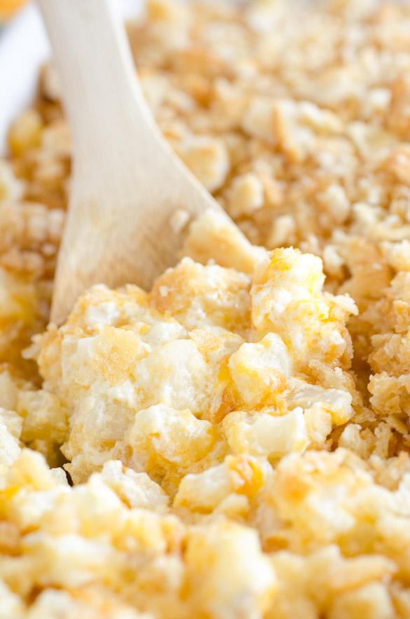 wooden spoon in cheesy potato casserole dish