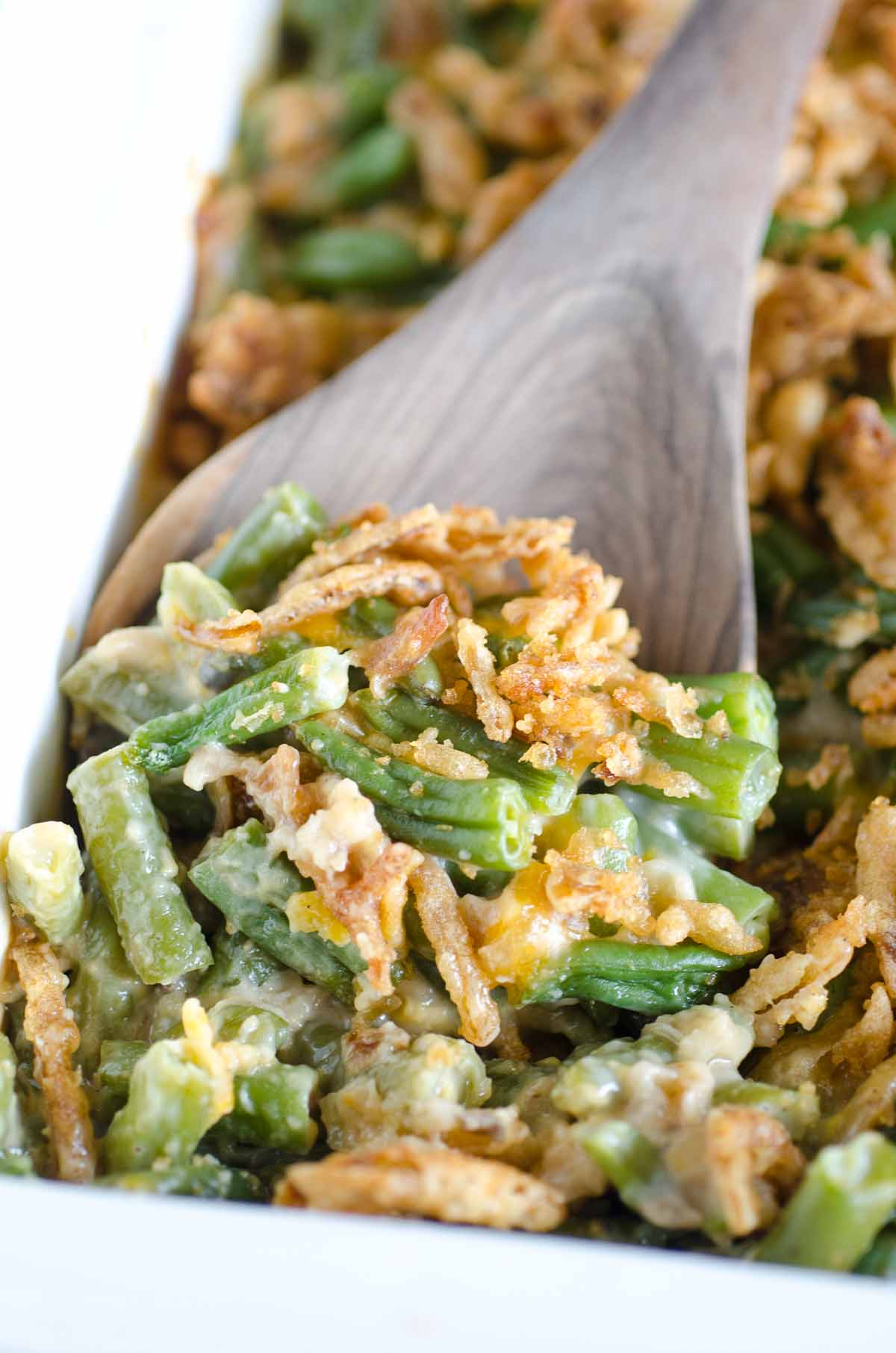 a wooden spoon scooping green bean casserole from pan
