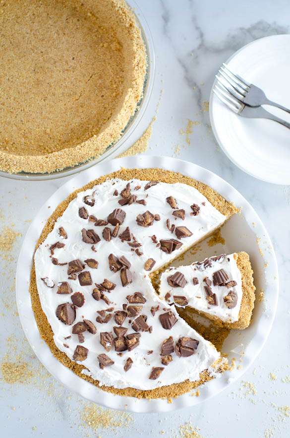 peanut butter pie and graham cracker pie crust overhead shot with plate and forks in background