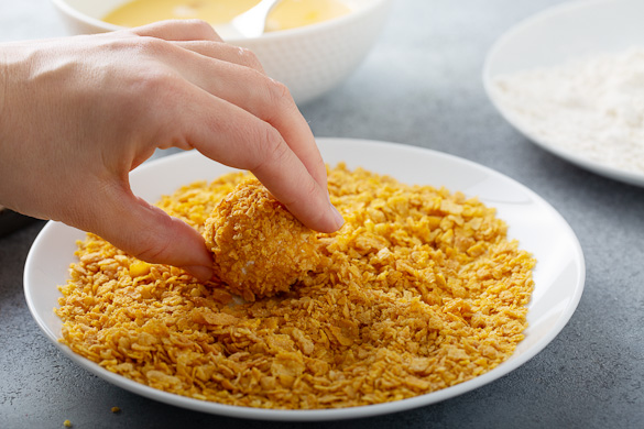 dipping chicken bite into cornflakes coating
