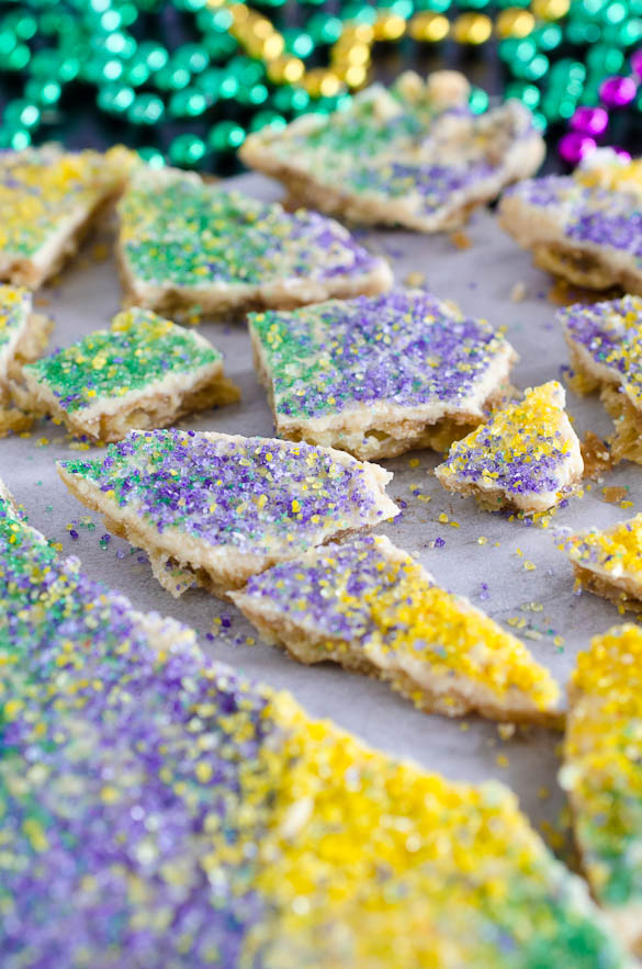 king cake cracker candy with mardi gras beads in background