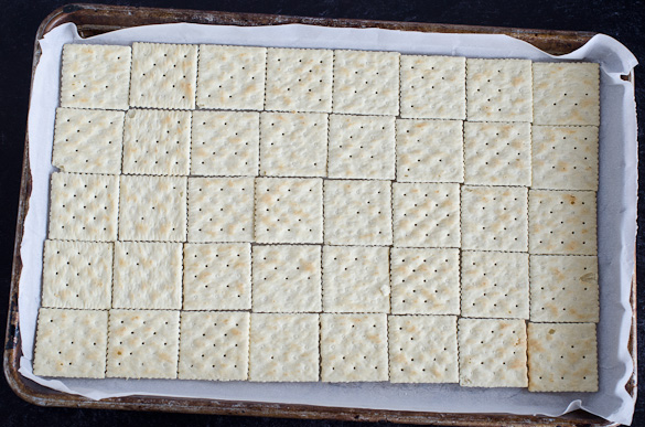 saltine crackers lined side by side on baking sheet