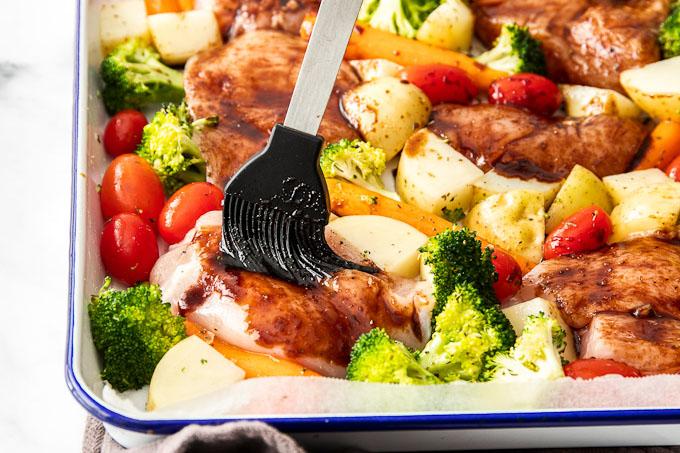 brushing glaze over chicken and veggies on baking sheet