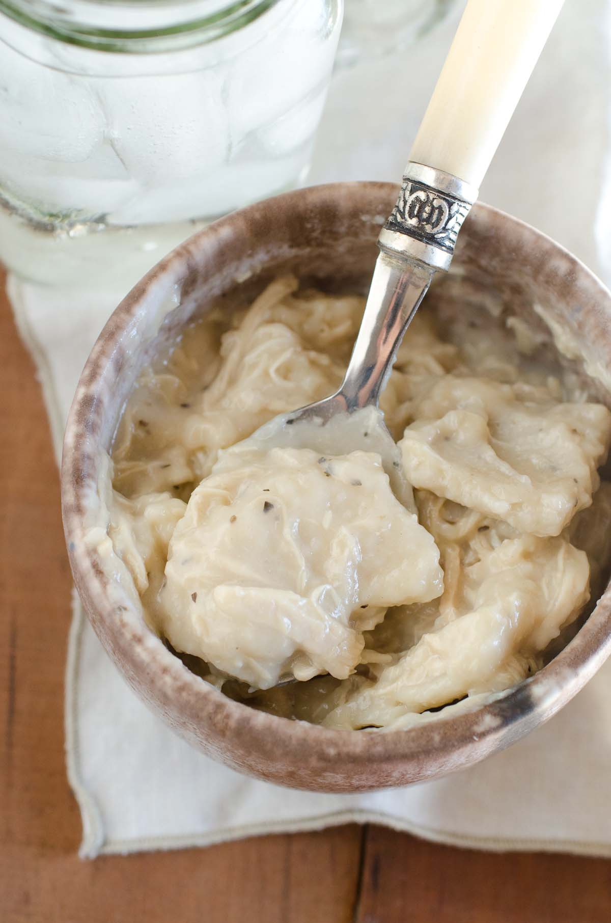 bowl of chicken and dumplings with spoon