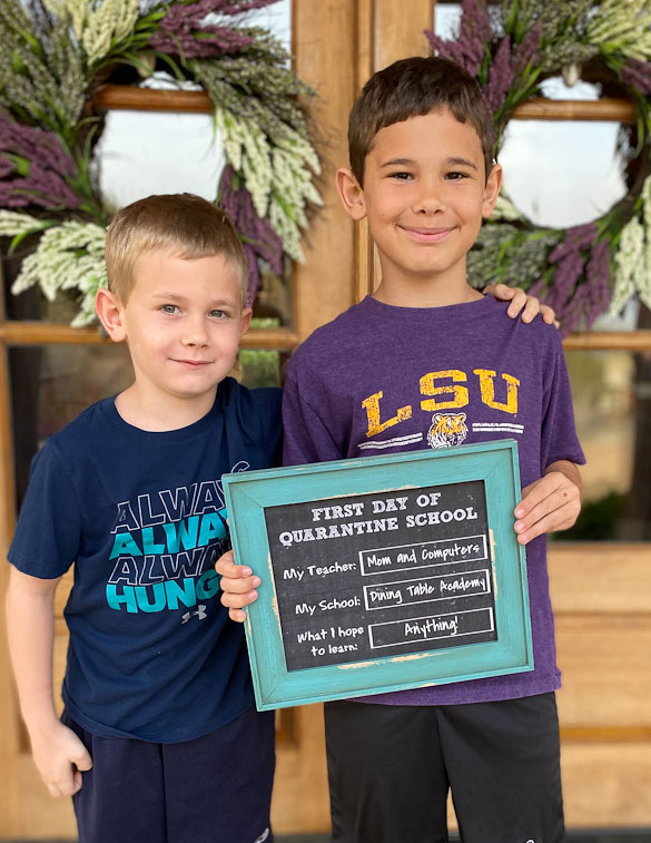 two kids with first day quarantine school sign