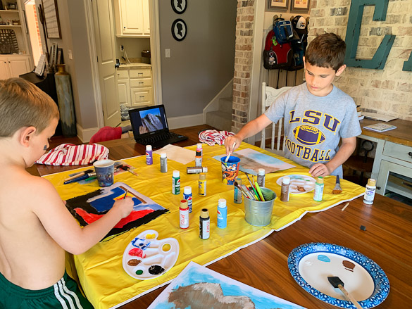 kids painting at table with art supplies and yellow tarp