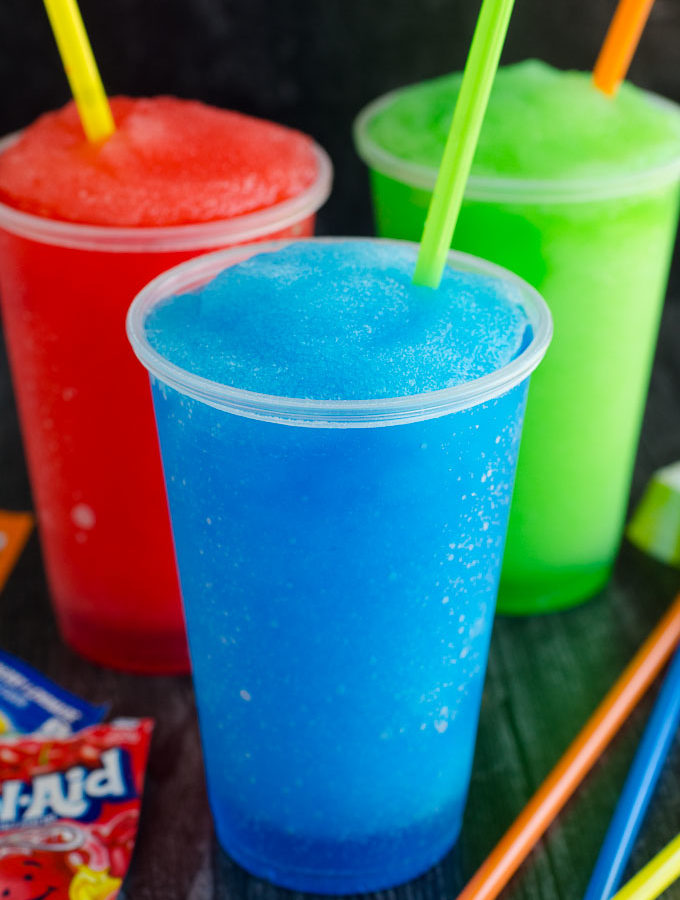 blue red and green slushies in plastic cups with straws and kool-aid packet