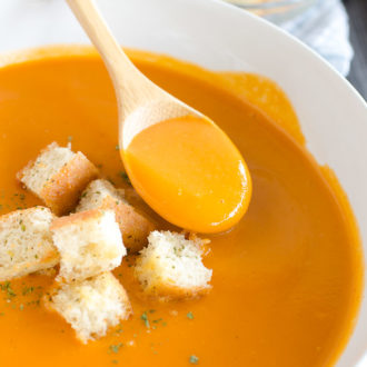 spoon in a bowl of tomato soup with croutons