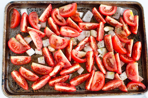 sliced tomatoes and onions on a baking sheet