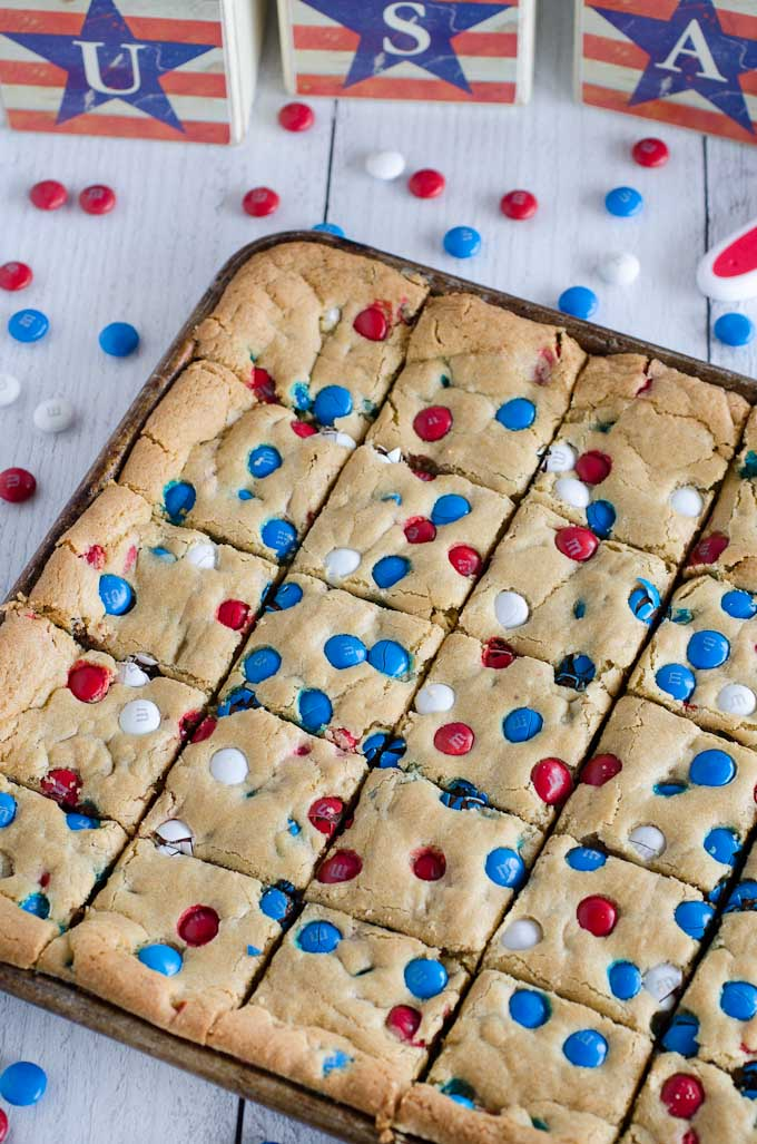 cookie bars in sheet pan with red white and blue M&M's and USA sign