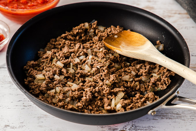 browning beef and onions in skillet with wooden spatula