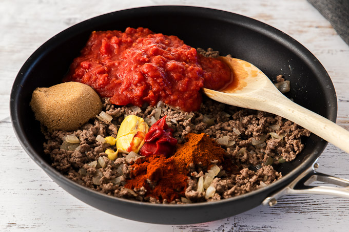 adding ingredients to ground beef in skillet