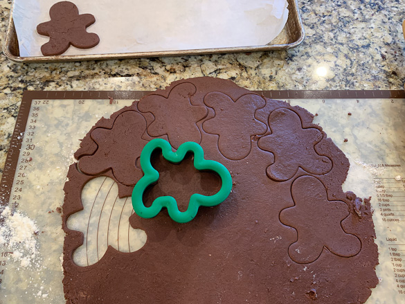 gingerbread man cookie cutters on chocolate dough