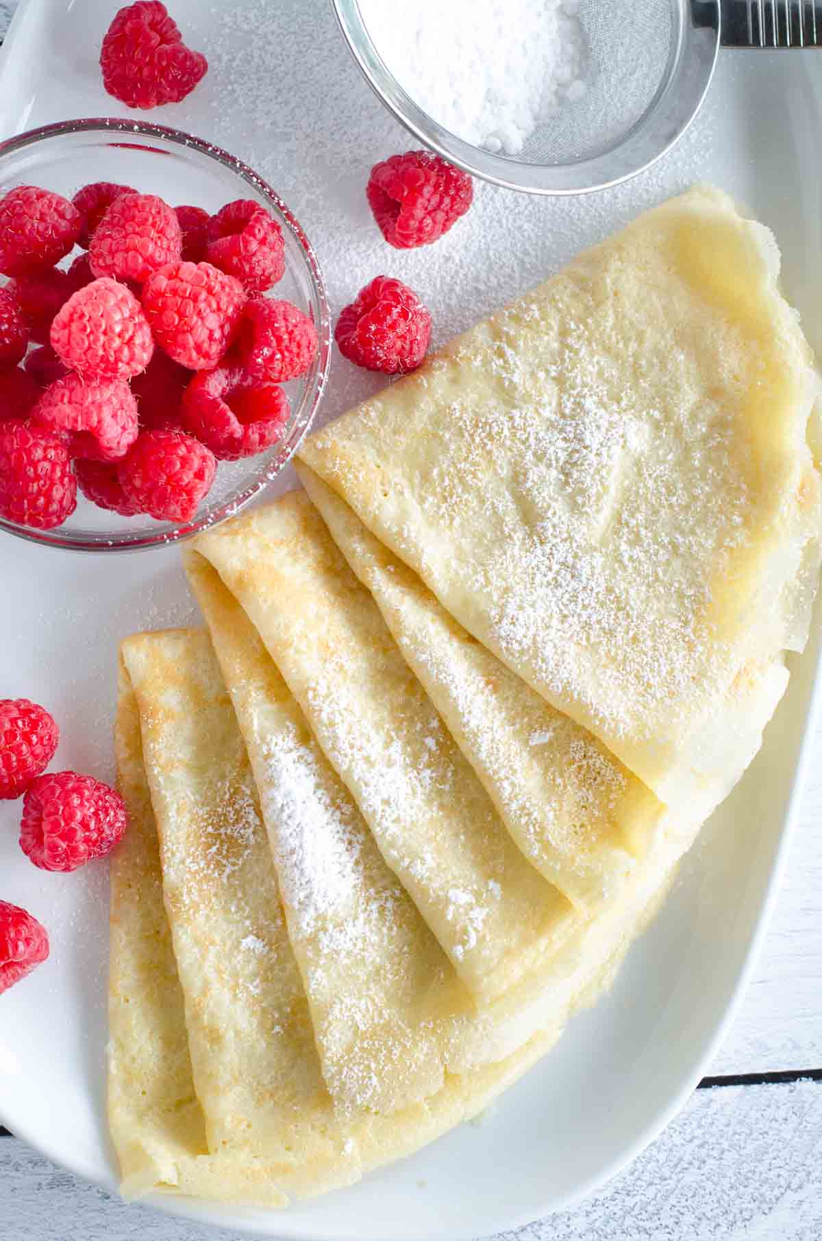 crepes folded on plate with raspberries