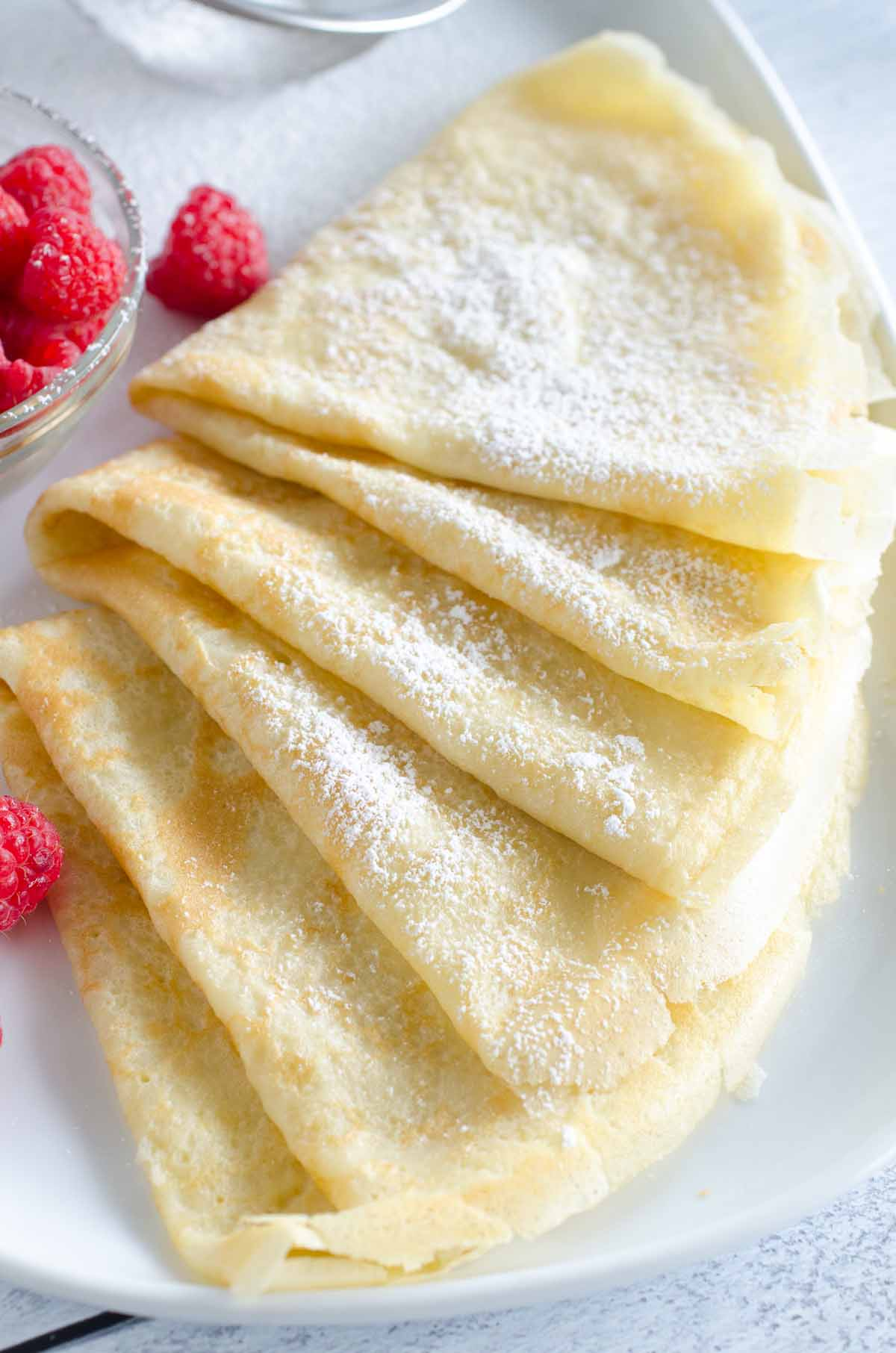 crepes folded on plate with raspberries and dusted with powdered sugar