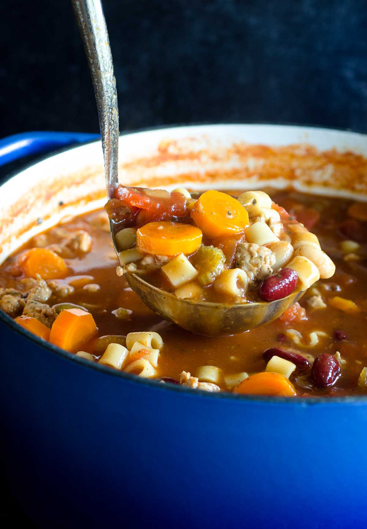 ladle full of vegetable soup in blue dutch oven