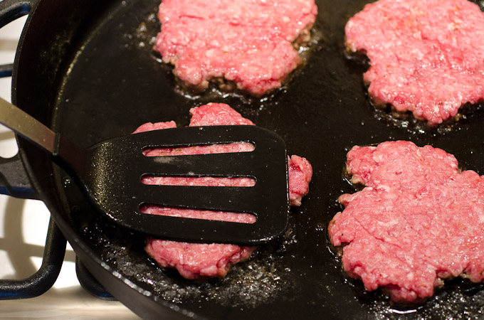 smashing burgers in skillet with spatula