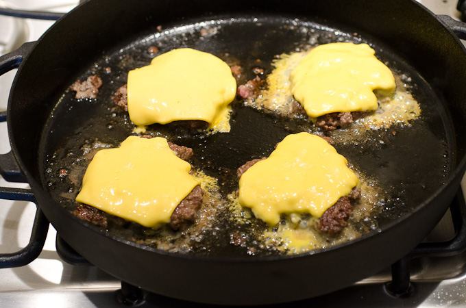 melted cheese on burgers in skillet