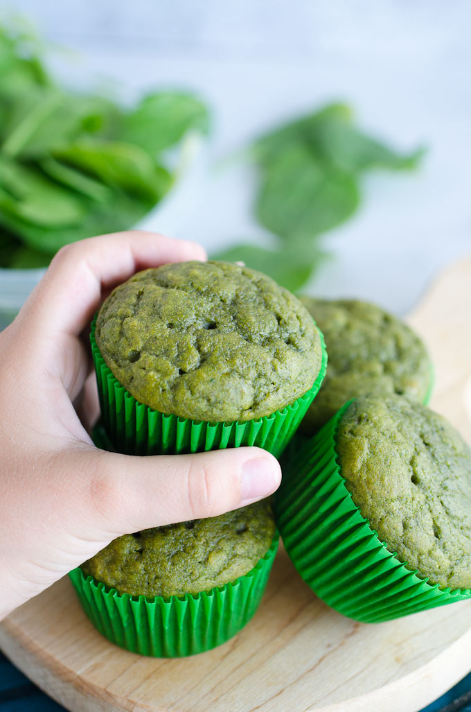 hand grabbing green spinach muffin from stack