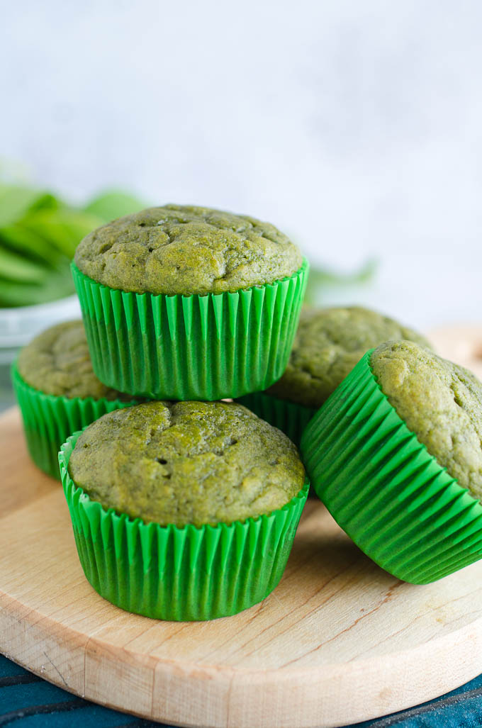 green spinach muffins stacked on cutting board