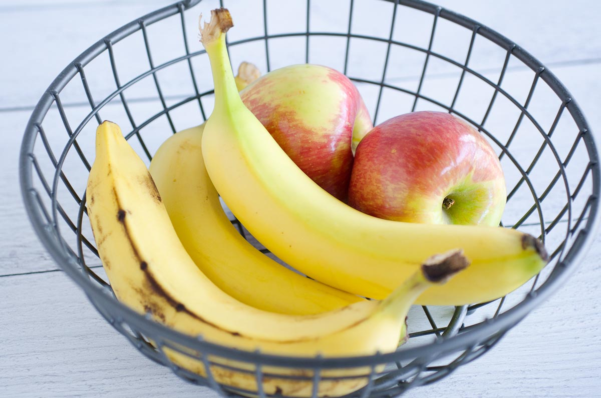 two unripe bananas in a fruit basket with apples and ripe banana