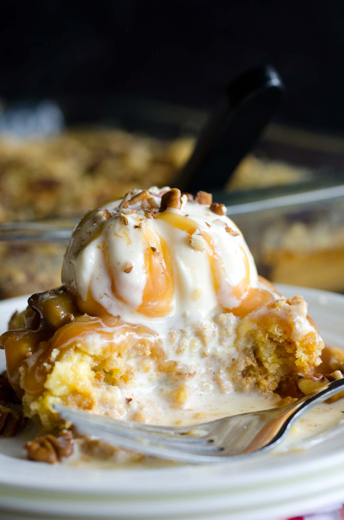 pumpkin cake with melting ice cream and caramel topping with pecans on a plate with fork