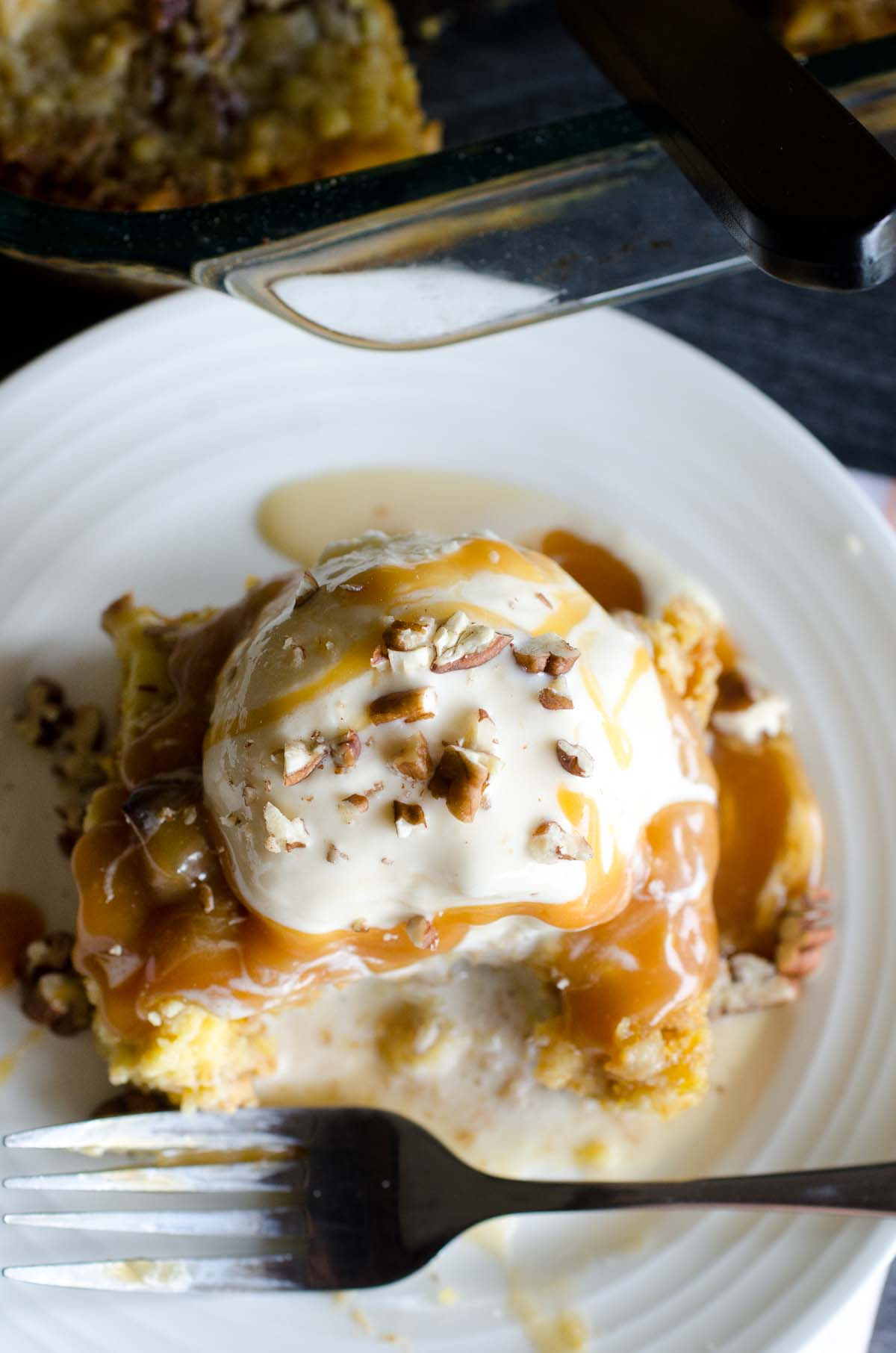 over shot of cake with ice cream, caramel and pecans on a plate with fork
