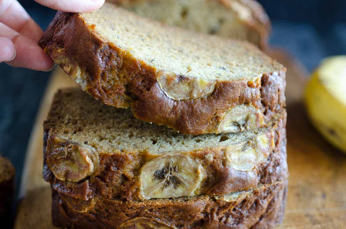 picking up slice of banana bread from cutting board