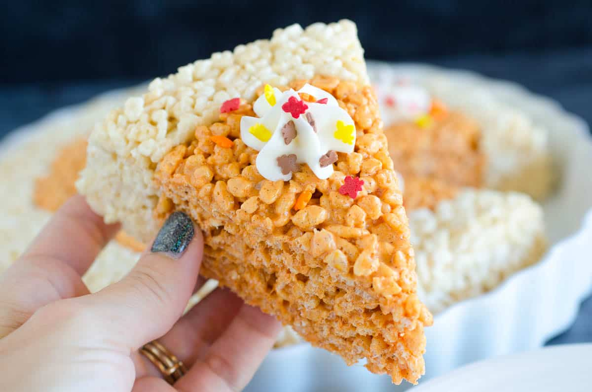 holding rice krispies treat that is shaped like a slice of pumpkin pie