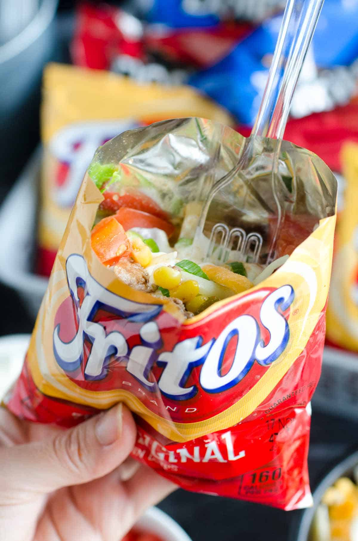 holding bag of fritos with taco fixins and fork inside