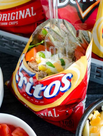 bag of fritos with taco fixins and fork