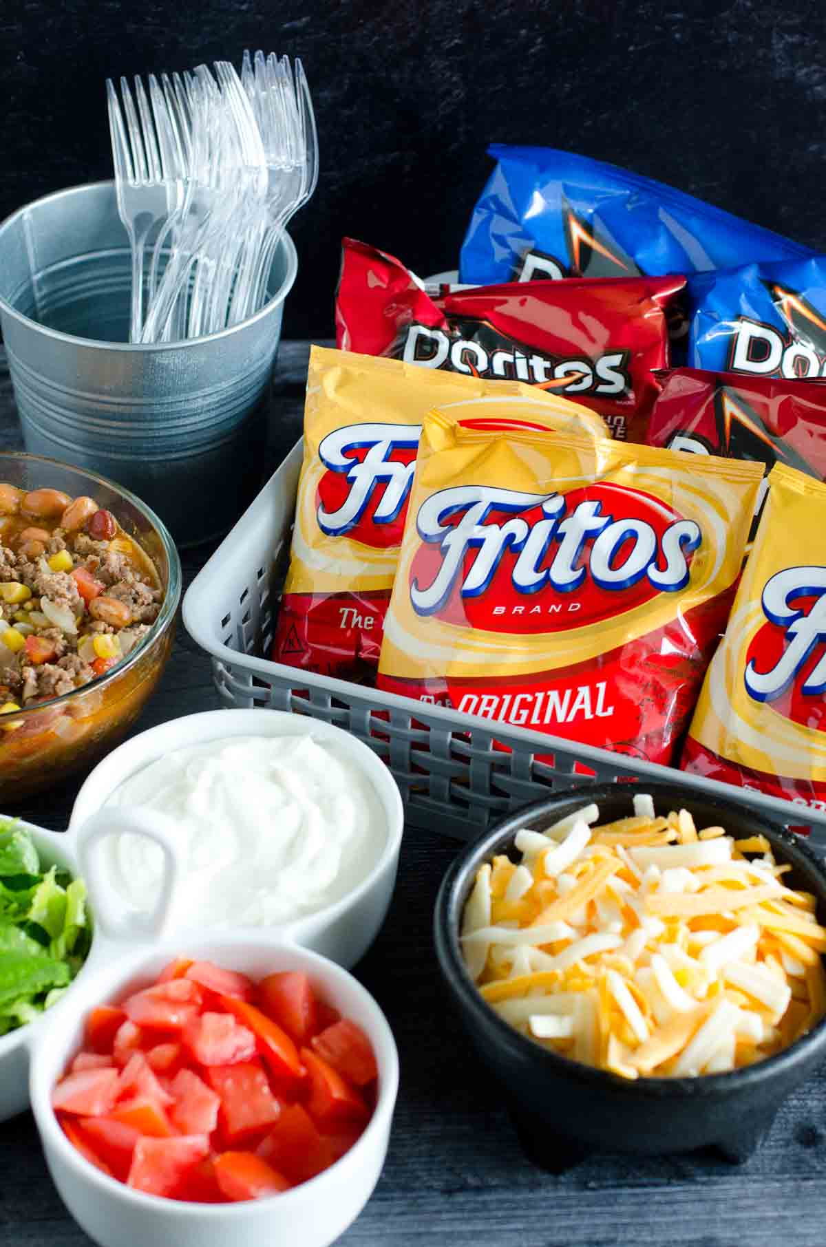 set up for walking taco bar with bags of chips and taco toppings in serving bowls