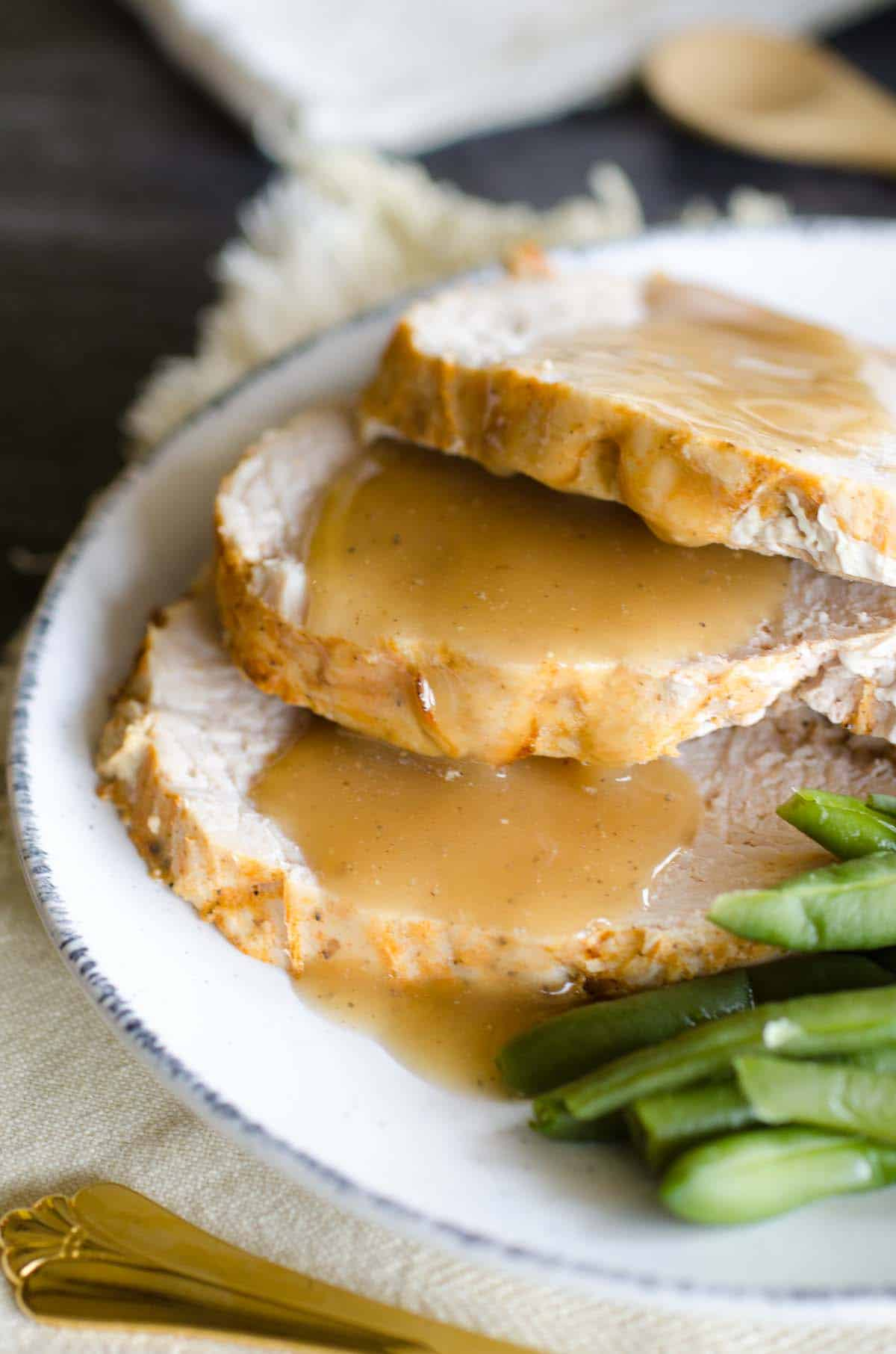 gravy over sliced turkey on a plate with green beans
