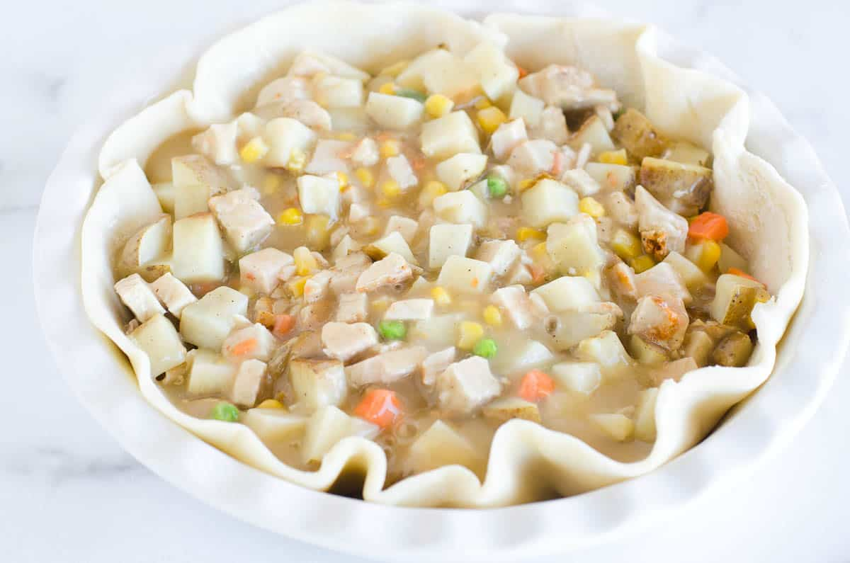 pie crust with turkey pot pie filling ready for oven