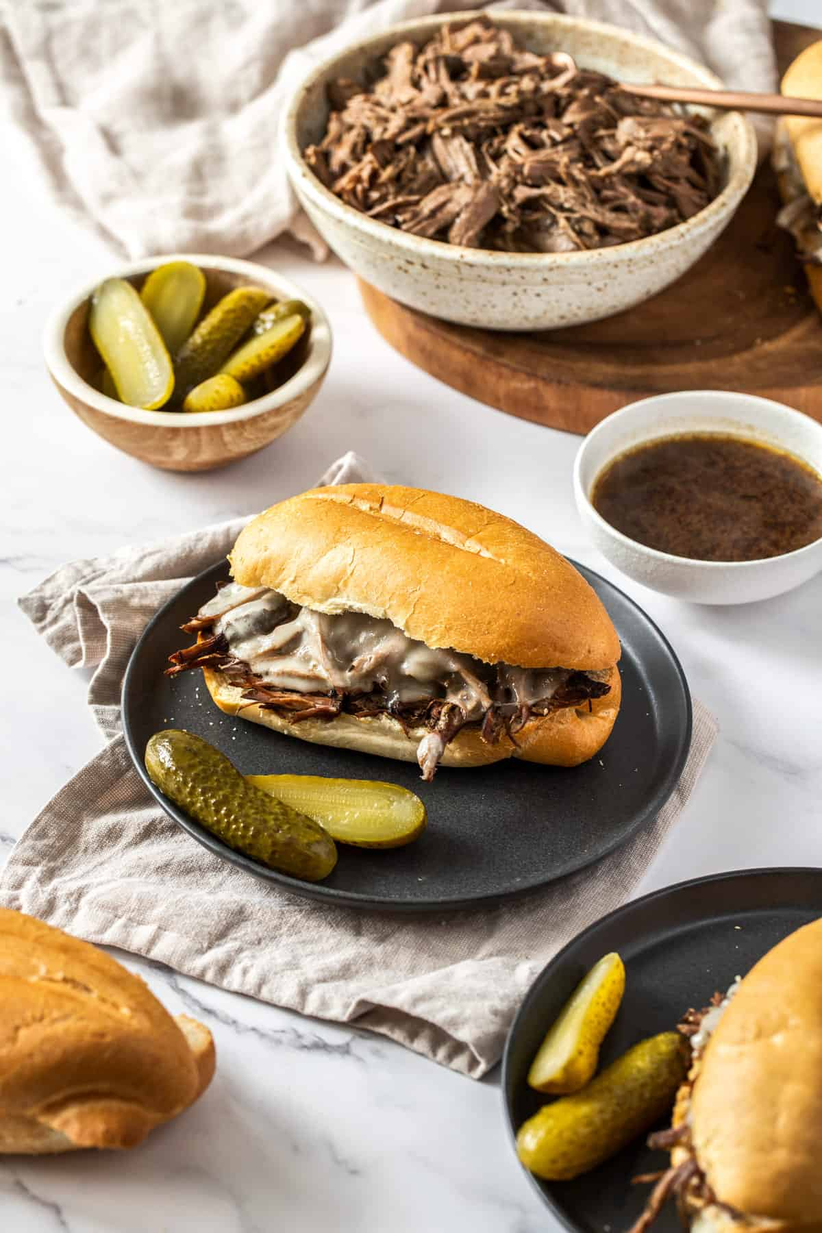 beef dip sandwich plated with pickles and au jus