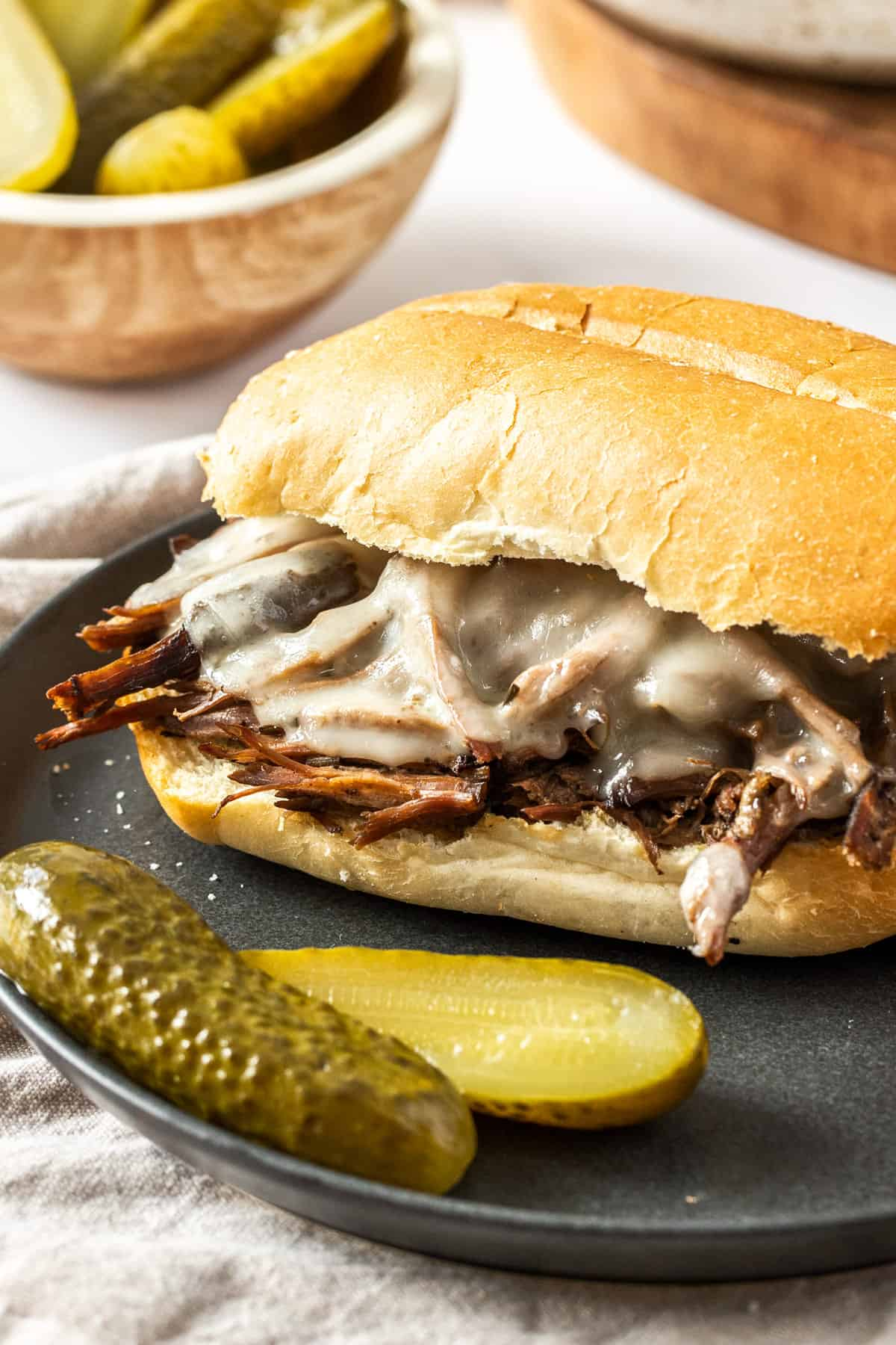 french dip sandwich on a plate with melty cheese