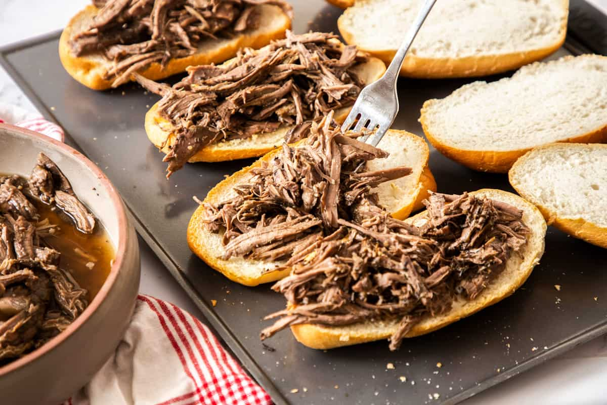 topping hoagie rolls with shredded beef on baking sheet