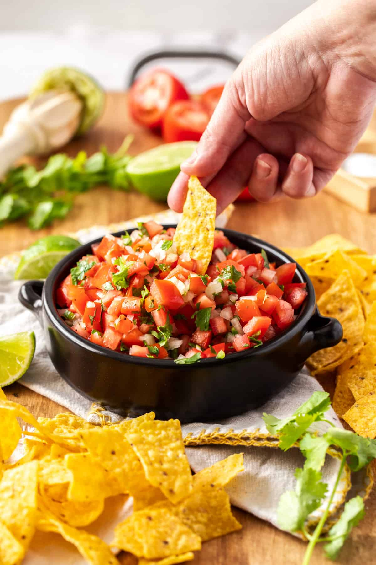 chip dipped in a bowl of pico de gallo surrounded by more ingredients