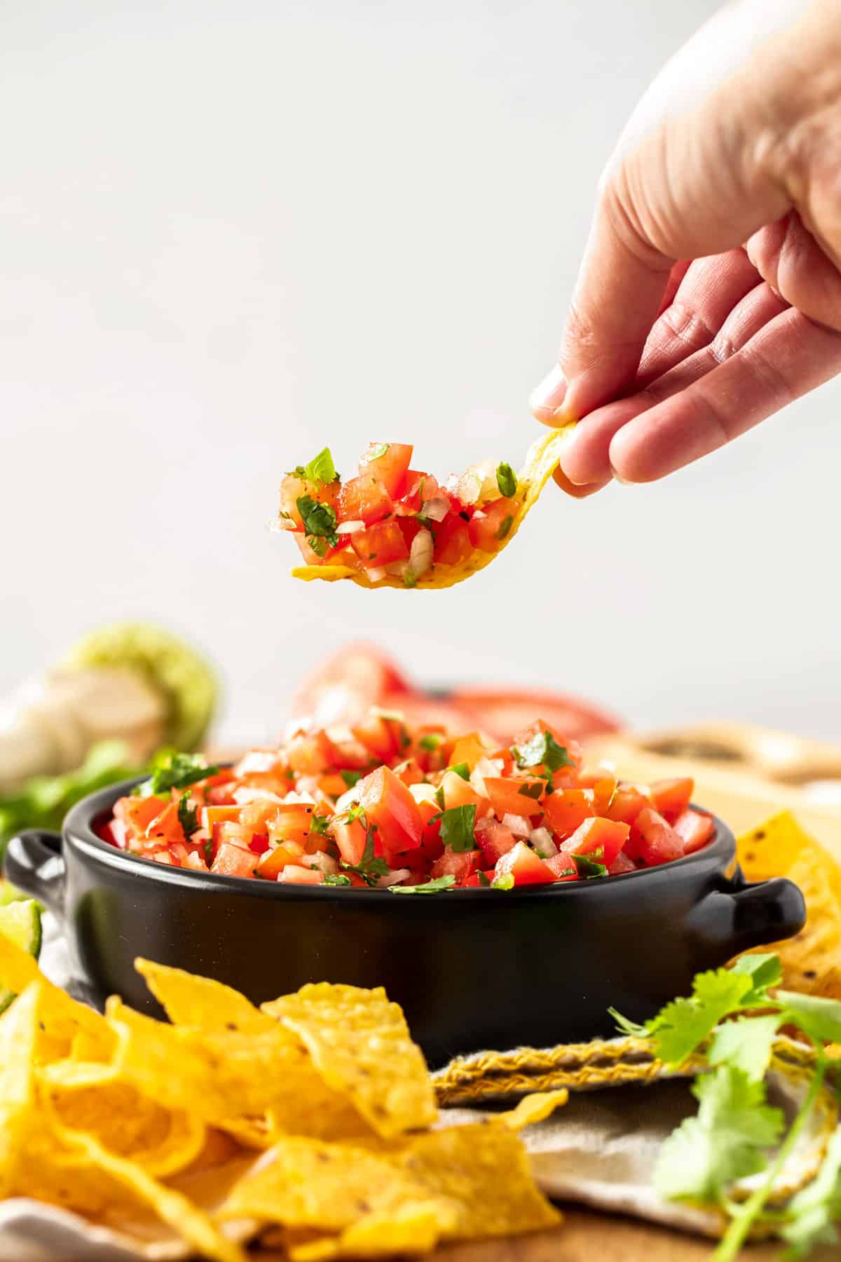 chip dipped into bowl of pico de gallo surrounded by more chips