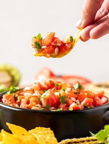 chip dipped into a bowl of pico de gallo salsa